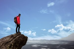Man standing on mountain peak looking outwards
