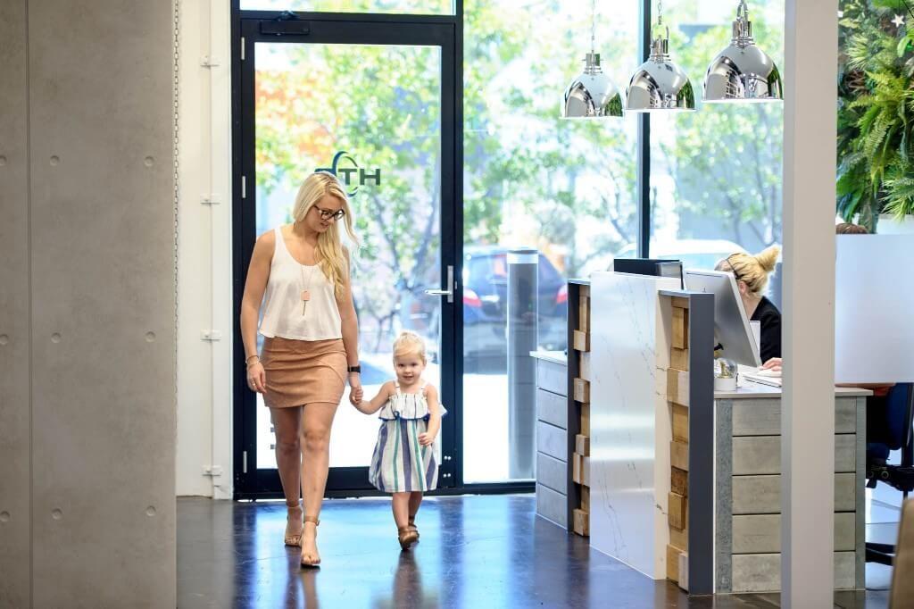 Young mum walking daughter through work.