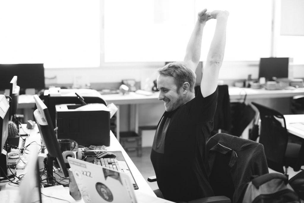 Man stretching at work.